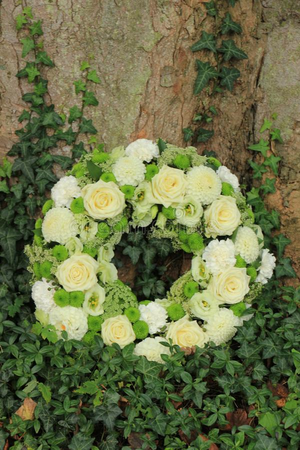 White sympathy wreath near a tree. White sympathy wreath or funeral flowers near a tree, white roses and mums royalty free stock photography