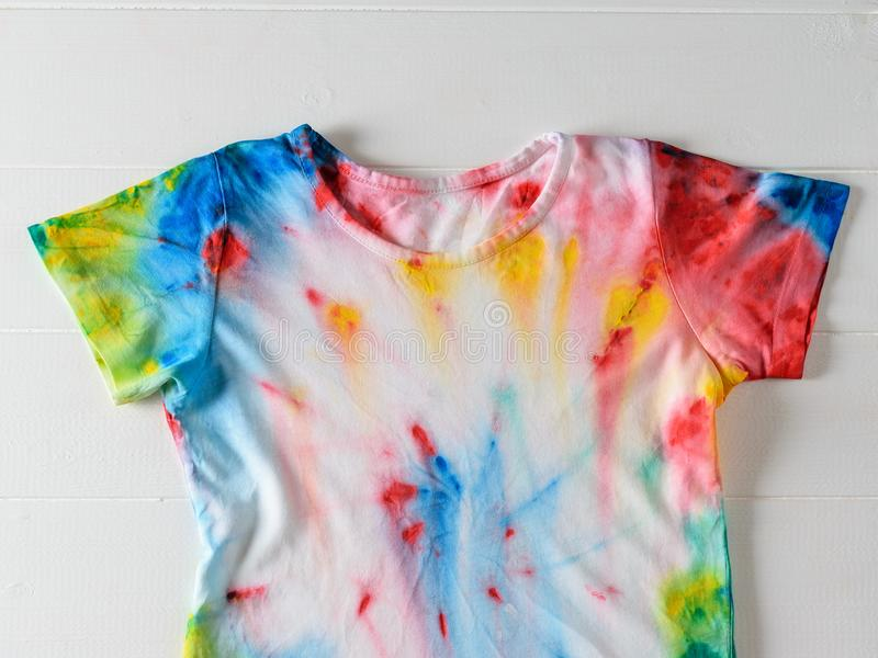 White t-shirt hand painted in tie dye style on white wooden table. royalty free stock image