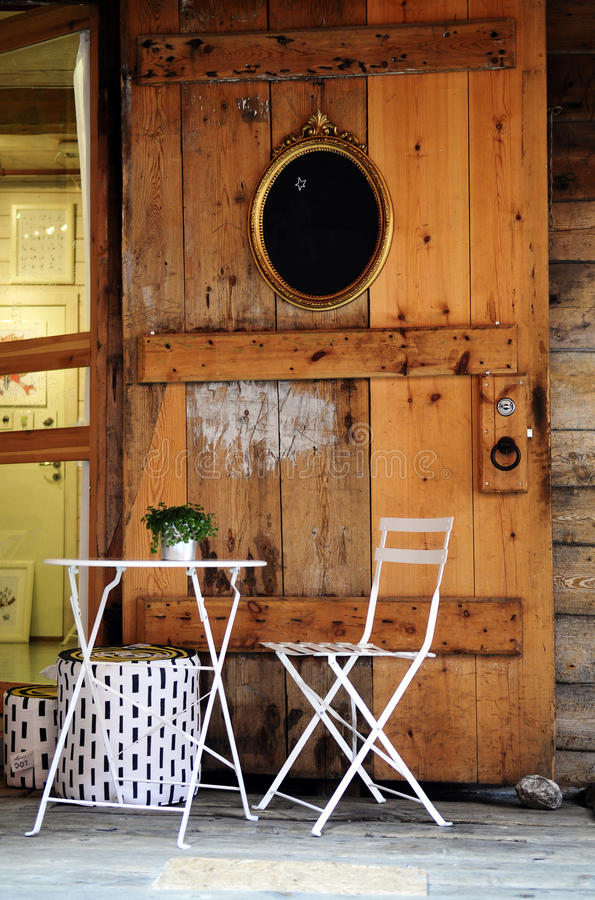 White Table and Chair with Green Plant. Honey wooden door with an oval golden frame with black slate. White chair and table with small potted green plant on top stock photos