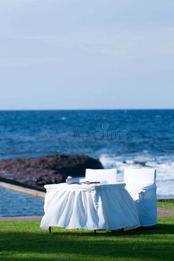 White table and chairs by the seaside royalty free stock photo