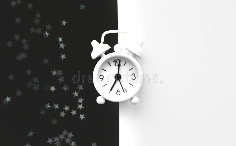 White table clock, alarm on black white background, top view. Good morning. Minimalism.  royalty free stock images