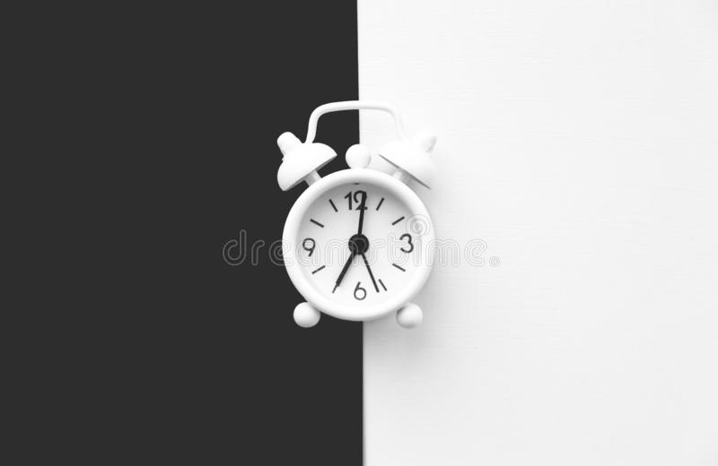 White table clock, alarm on black white background, top view. Good morning. Minimalism.  royalty free stock photography