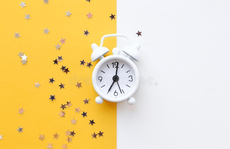 White table clock, alarm on yellow background, top view. Good morning. Minimalism, flatlay. White table clock, alarm on yellow background, top view. Good morning royalty free stock image