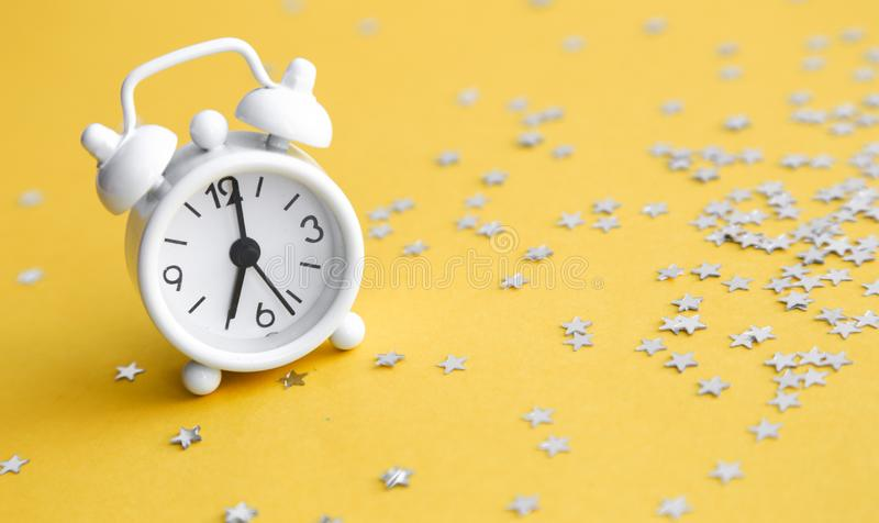 White table clock, alarm on yellow background, top view. Good morning. Minimalism, flatlay. White table clock, alarm on yellow background, top view. Good morning stock images