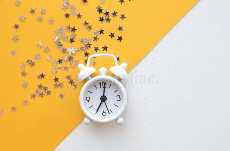 White table clock, alarm on yellow background, top view. Good morning. Minimalism, flatlay. White table clock, alarm on yellow background, top view. Good morning royalty free stock photo