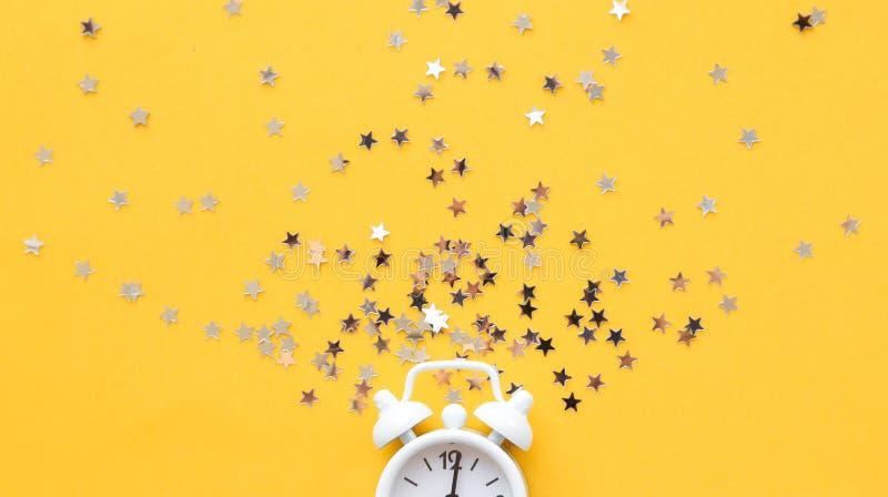White table clock, alarm on yellow background, top view. Good morning. Minimalism, flatlay. White table clock, alarm on yellow background, top view. Good morning stock image