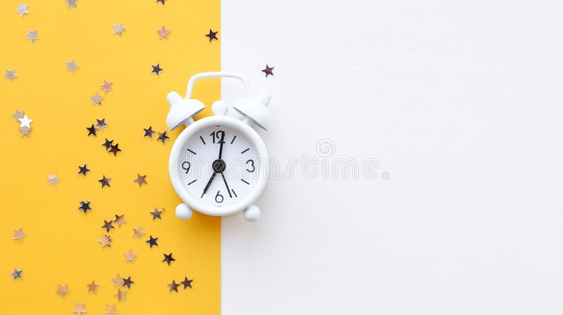 White table clock, alarm on yellow background, top view. Good morning. Minimalism, flatlay. White table clock, alarm on yellow background, top view. Good morning royalty free stock images