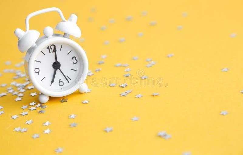 White table clock, alarm on yellow background, top view. Good morning. Minimalism, flatlay. White table clock, alarm on yellow background, top view. Good morning stock photos