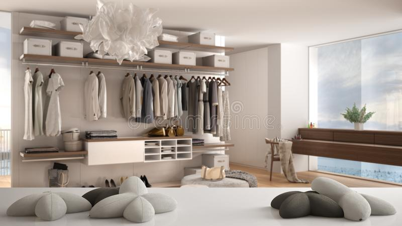White table, desk or shelf with five soft white pillows in the shape of stars or flowers, over blurred bedroom with walk-in closet. Minimalist architecture stock illustration