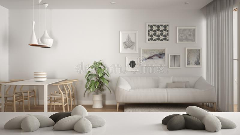 White table, desk or shelf with five soft white pillows in the shape of stars or flowers, over blurred modern living room, white. Architecture interior design stock photography
