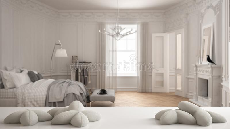 White table, desk or shelf with five soft white pillows in the shape of stars or flowers, over blurred classic bedroom, white arch stock illustration