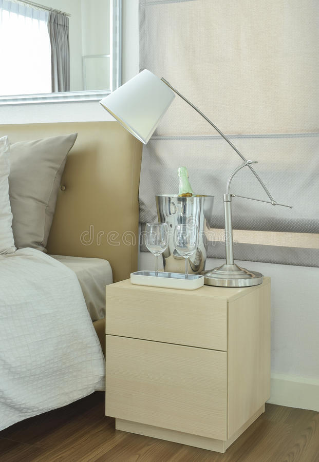White table lamp with empty glasses and wine bottle on table. White table lamp with empty glasses and wine bottle on bed side table royalty free stock photo