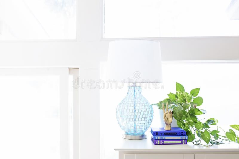 White Table Lamp on Sideboard Near Plant and Books stock photo