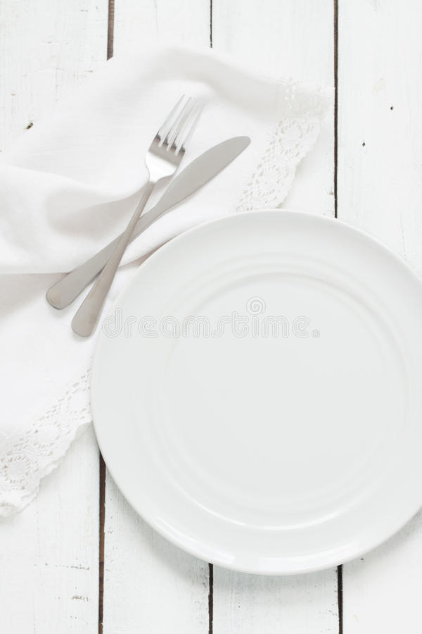 White table setting from above. Empty plate, cutlery, napkin on white. royalty free stock images