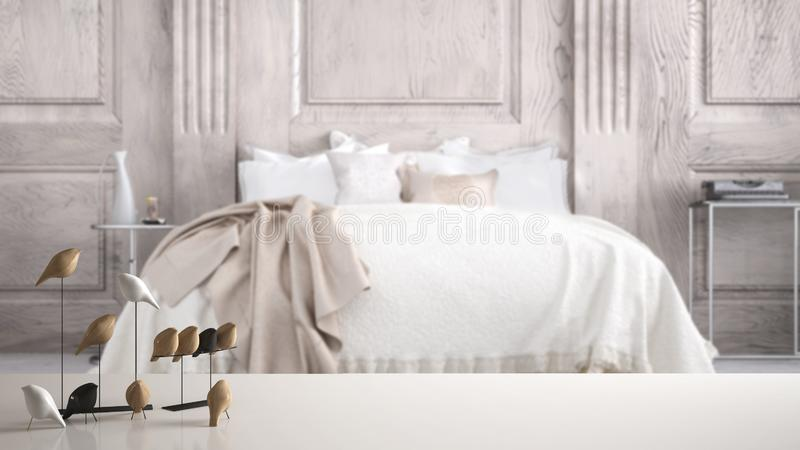 White table top or shelf with minimalistic bird ornament, birdie knick - knack over blurred classic bedroom with double bed. Modern interior design stock image