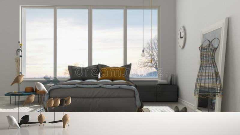 White table top or shelf with minimalistic bird ornament, birdie knick - knack over blurred contemporary bedroom with big panorami. C window, modern interior stock photo