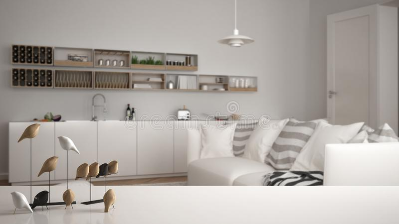 White table top or shelf with minimalistic bird ornament, birdie knick - knack over blurred contemporary living room. With kitchen, modern interior design stock photos