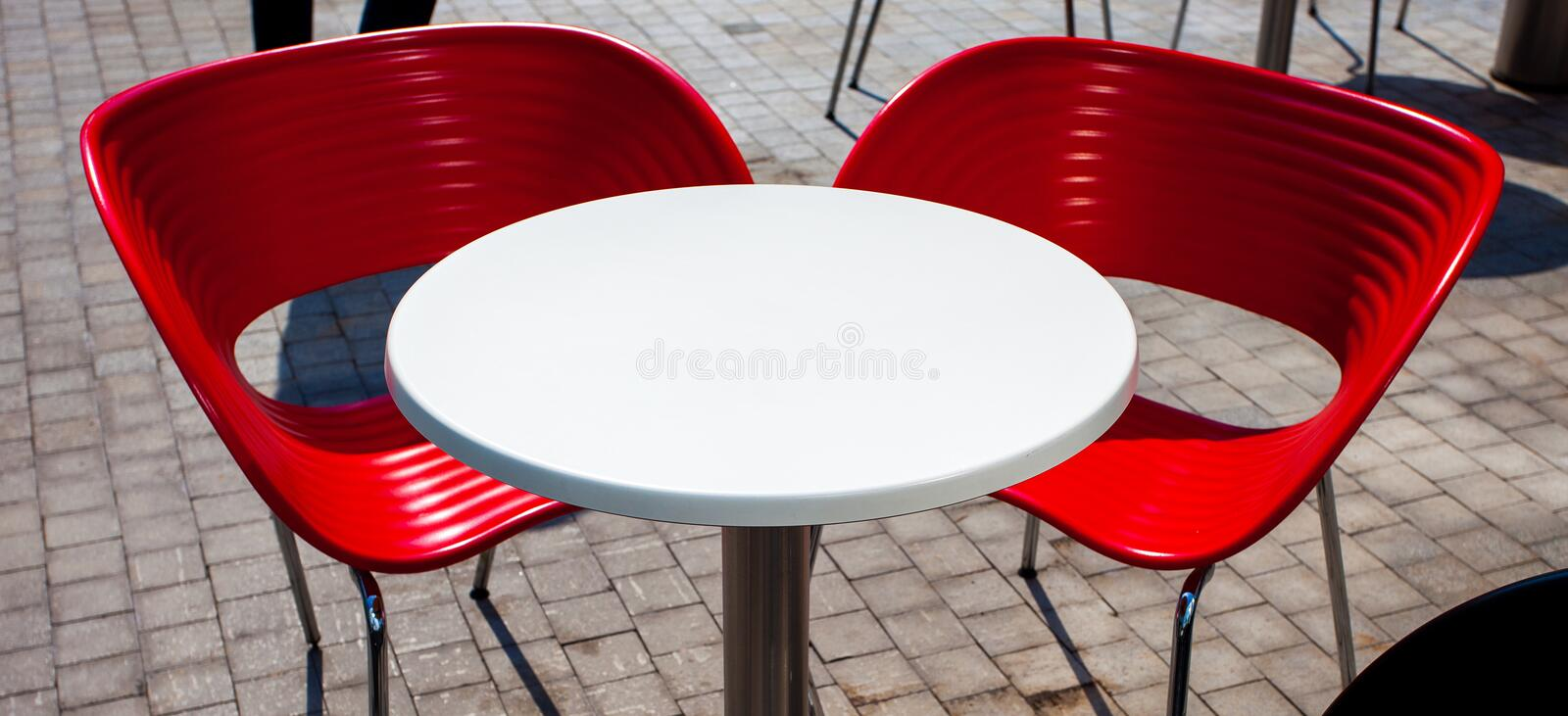 White table, two red chairs in street cafe. White table, two red chairs at an outdoor cafe. copy space stock images