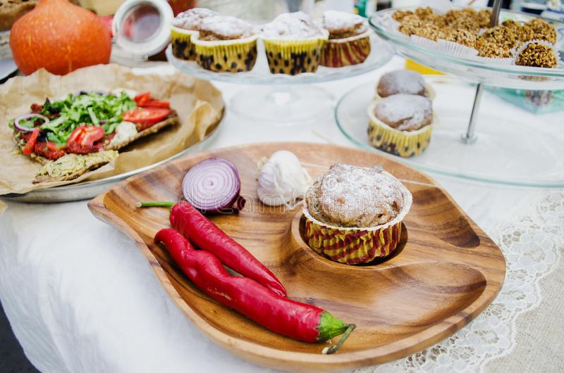Muffin with sugar powder and chilli pepper on a wooden plate stock photo
