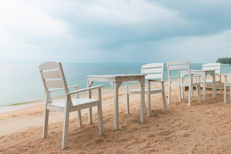 Romantic cafe with white tables and chairs on the sea shore. White tables and chairs in a beach cafe on the romantic sea shore with tropical storm rainy sky on stock image
