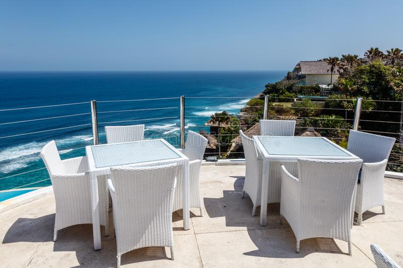 White tables and chairs at a outdoor cliff cafe with ocean view royalty free stock image
