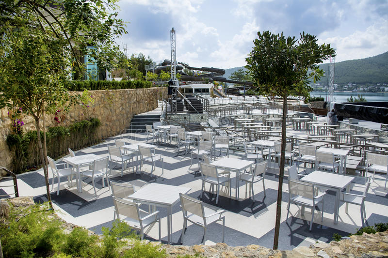 White tables and chairs.Outdoor restaurant. White wooden tables and chairs.Outdoor restaurant royalty free stock photo