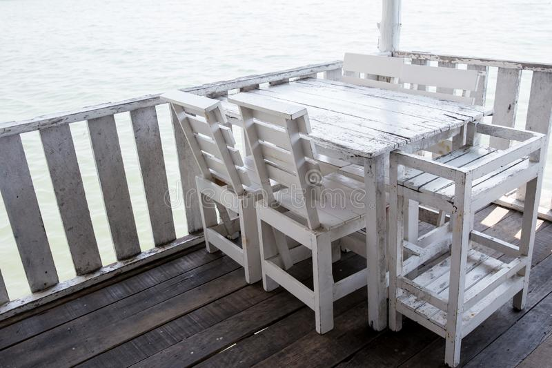 White tables and chairs in restaurant. empty rattan furniture coffee set table chair at wooden floor sea front by the sea. royalty free stock photography