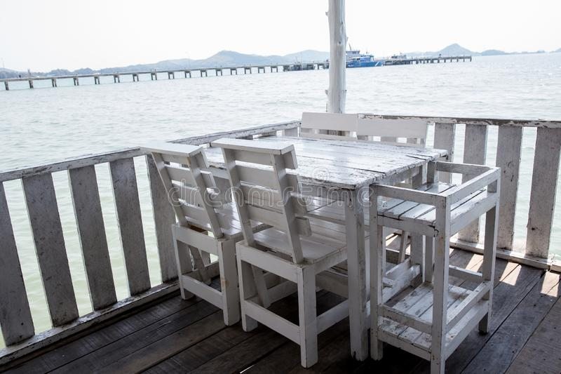 White tables and chairs in restaurant. empty rattan furniture coffee set table chair at wooden floor sea front by the sea. stock photos