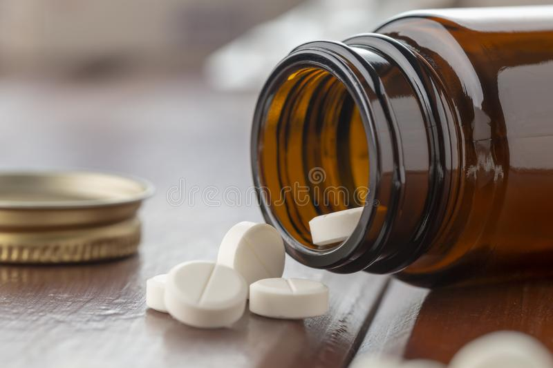 White tablet inside an open glass bottle with tablets. Close-up on the last pill stock photography