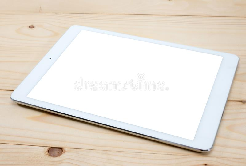 White tablet PC with blank screen on wooden table royalty free stock photo
