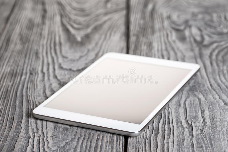 White tablet on a wooden table stock image