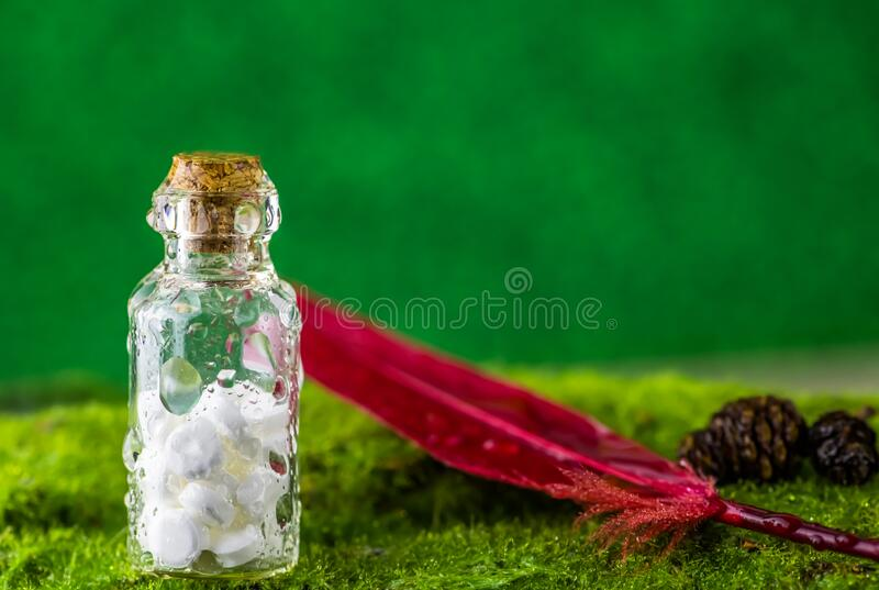 White tablets in a bottle of water droplets on green background. Banner White tablets in a bottle of water droplets and red feather on green background. Rain stock images