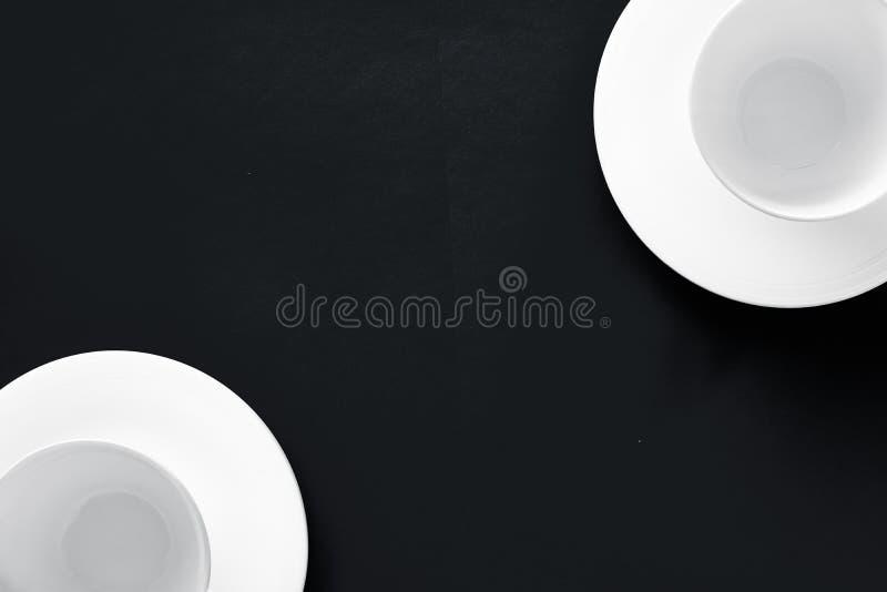 White tableware crockery set, empty cup on black flatlay background royalty free stock photo