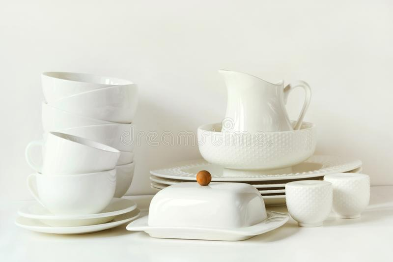White tableware for serving. Crockery,dish, utensils and other different white stuff on white table-top. Kitchen still life as bac royalty free stock photography