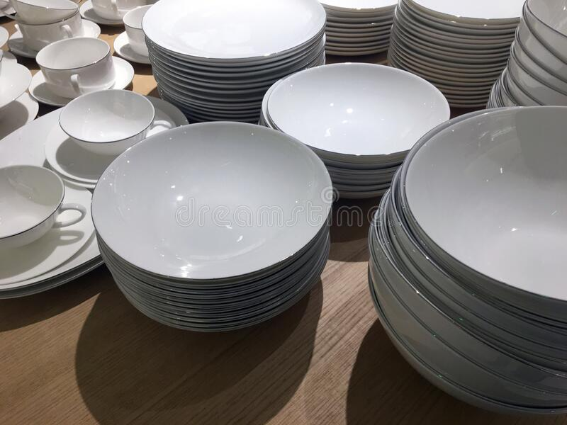 White tableware in the store. Different bowls. Varieties of white tableware in the store. The concept of choosing dishes, sales, promotions. Earthenware ceramics stock photo