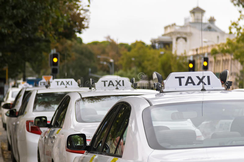 White taxi cars parking along the footpath in Adelaide, Australia. With blurred background royalty free stock photos