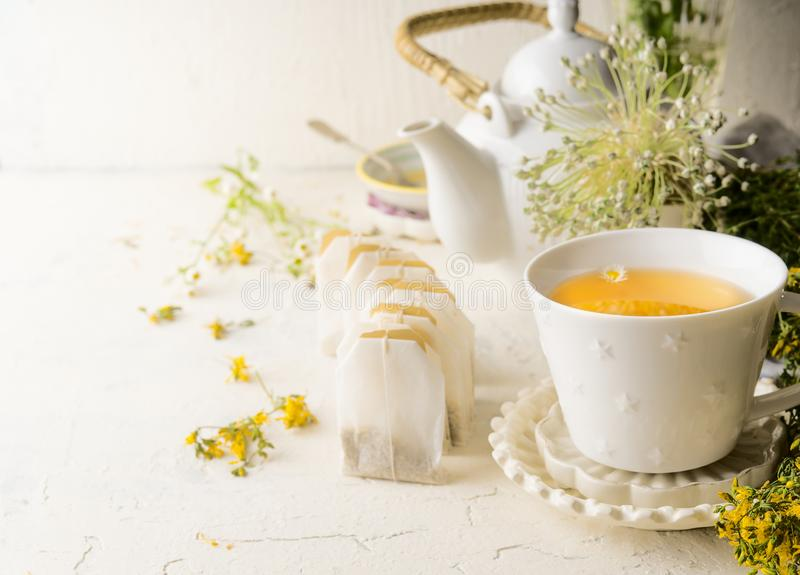 White tea cup with tea bags of herbal tea standing  on white table with teapot and fresh medical herbs and flowers. Close up. stock photography