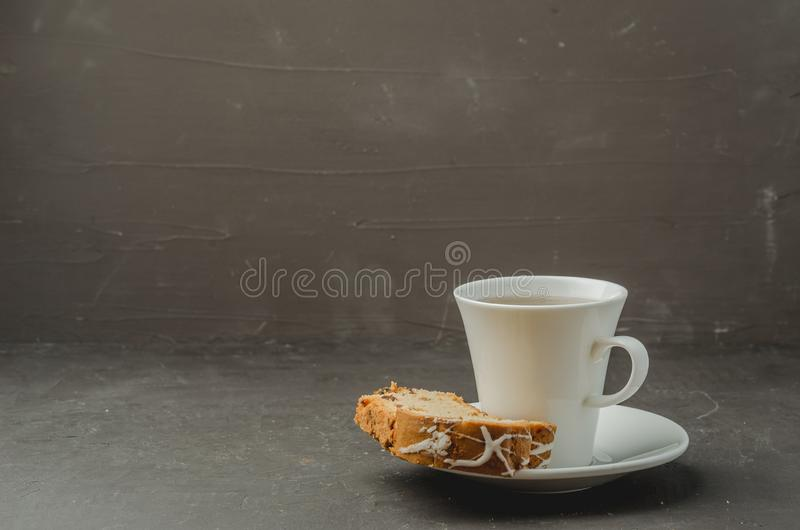 White tea cup and pastries piece on dark stone table. Copyspace for your text. Mug, drink, pastry, breakfast, cake, dessert, sweet, bun, baked, homemade, cut royalty free stock photography