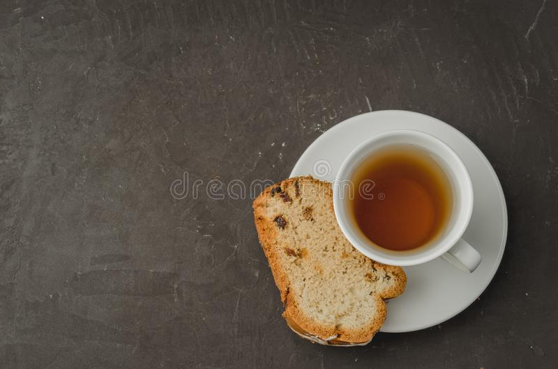 White tea cup and pastries piece on dark stone table. Top view with copyspace for your text. Mug, drink, pastry, breakfast, cake, dessert, sweet, bun, baked royalty free stock images