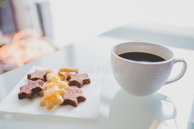 White Tea Cup Beside White Square Saucer With Star Shaped Cookies royalty free stock photos