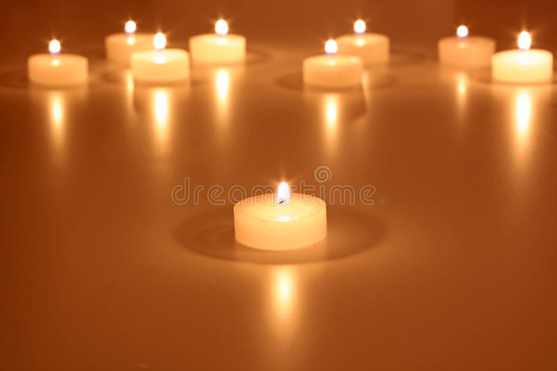 White tea lights as a Christmas decoration. White tea lights against a golden background as a Christmas decoration stock images