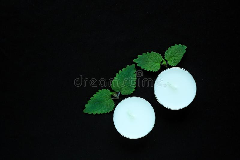 White tealight candles on black background. Beauty, SPA treatment, massage therapy and relax concept stock image