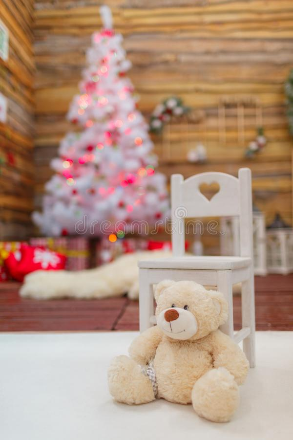 White teddy bear next to a chair close-up in a festive room. With a smart Christmas tree and presents royalty free stock photo