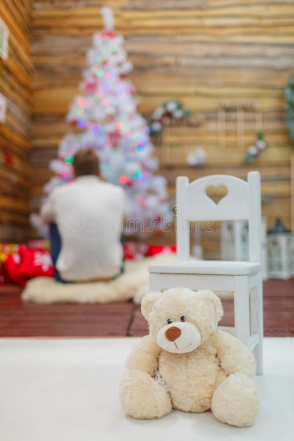White teddy bear next to a chair in a festive room. White teddy bear next to a chair in the festive room in the background guy in front of a smart Christmas tree royalty free stock photo