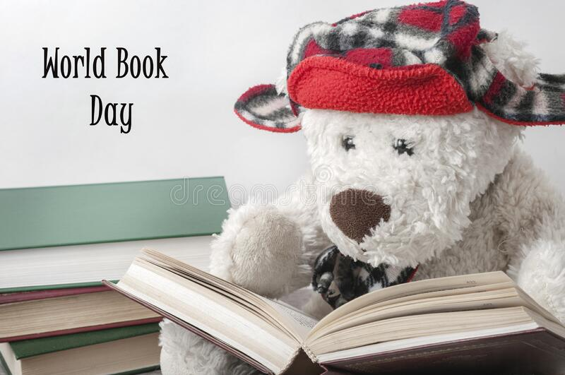 A white Teddy bear in a red hat is reading a book. Next to it is a stack of books. World book day stock photo