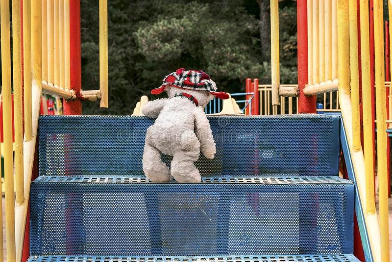 The white teddy bear in the red hat is understood by the blue stairs to the slide on the playground. royalty free stock photo