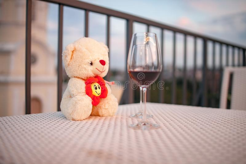 White teddy bear on table in cafe next to glass of red wine. Closeup. White teddy bear on table in cafe next to glass of red wine. Gift for St. Valentine`s Day stock image