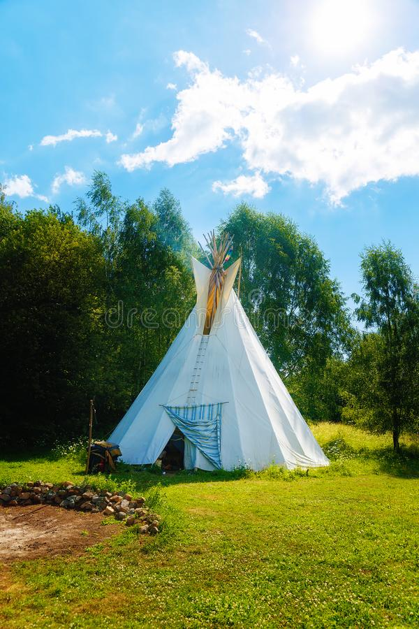 White teepee indian tent standing in beautiful summer landscape. White teepee indian tent standing in beautiful summer landscape stock image