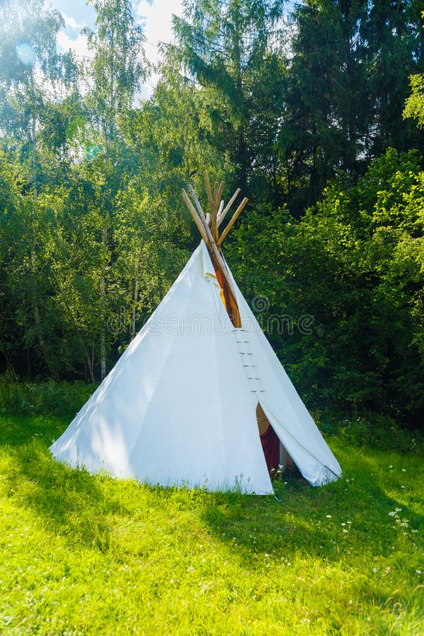 White teepee indian tent standing in beautiful summer landscape. White teepee indian tent standing in beautiful summer landscape royalty free stock image
