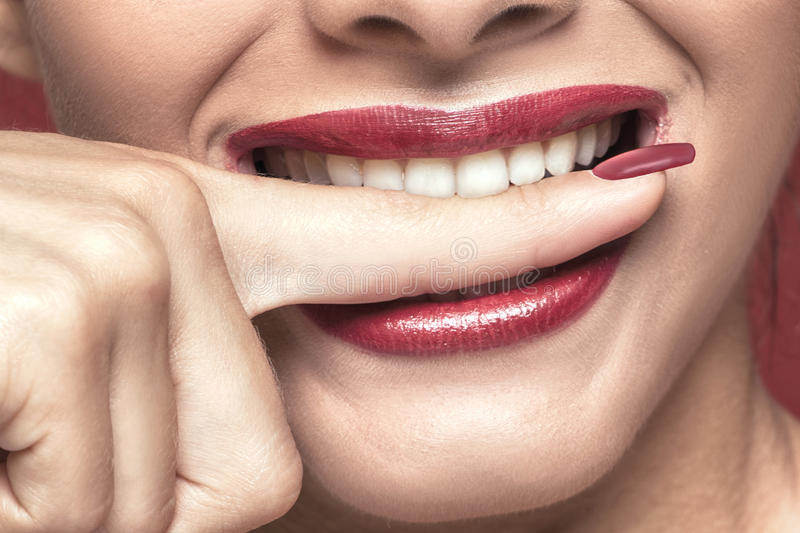 White teeths biting a finger. Closeup photo, white teeths biting a finger. Red lips royalty free stock images
